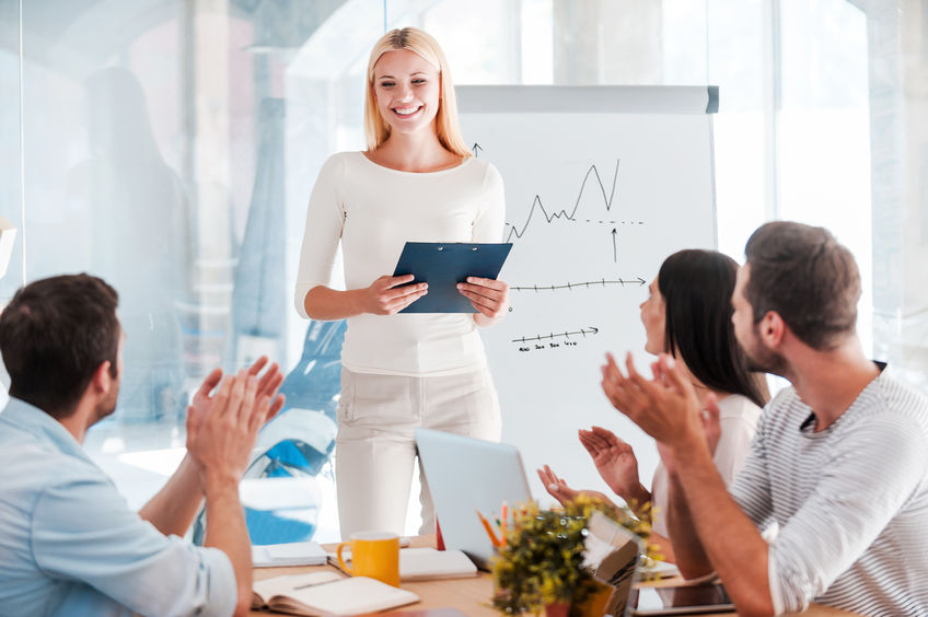 Great presentation! Cheerful young woman standing near whiteboard and smiling while her colleagues sitting at the desk and applauding